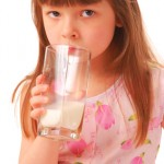 Girl with milk-moustache holding glass of milk